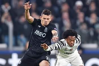 Juan Cuadrado disputa uma bola com Tiquinho Soares no jogo entre Juventus e FC Porto.