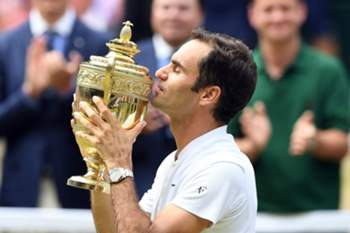 epa06091246 Roger Federer of Switzerland kisses the championship trophy following his victory over Marin Cilic of Croatia in the men's final of the Wimbledon Championships at the All England Lawn Tennis Club, in London, Britain, 16 July 2017. EPA/FACUNDO ARRIZABALAGA EDITORIAL USE ONLY/NO COMMERCIAL SALES