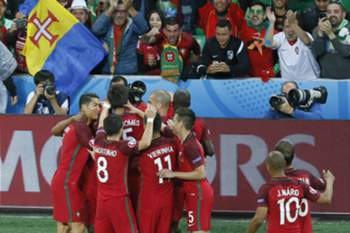 epa05365319 Portugal players celebrate after Nani (obscured) scored the 1-0 goal during the UEFA EURO 2016 group F preliminary round match between Portugal and Iceland at Stade Geoffroy Guichard in Saint-Etienne, France, 14 June 2016. (RESTRICTIONS APPLY: For editorial news reporting purposes only. Not used for commercial or marketing purposes without prior written approval of UEFA. Images must appear as still images and must not emulate match action video footage. Photographs published in online publications (whether via the Internet or otherwise) shall have an interval of at least 20 seconds between the posting.) EPA/SERGEY DOLZHENKO EDITORIAL USE ONLY