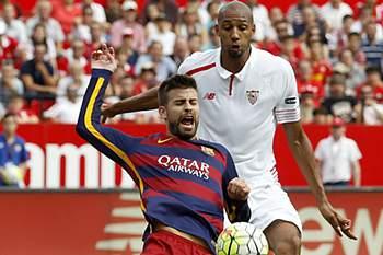 Gerard Piqué do Barcelona disputa a bola com o médio do Sevilha Steven N'Zonzi.