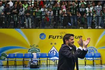 Treinador de futsal aplaude os adeptos.
