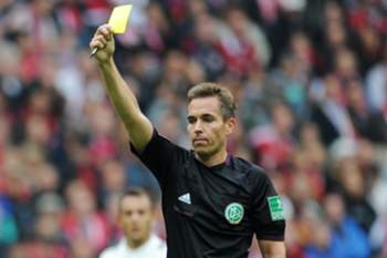 epa03867379 Referee Tobias Stieler shows Hanover's Marcelo Antonio Guedes (L)the yellow card during the match between FC Bayern Munich and Hannover 96 at Allianz Arena in Munich, Germany, 14 September 2013. (ATTENTION:Due to the accreditation guidelines, the DFL only permits the publication and utilisation of up to 15 pictures per match on the internet and in online media during the match.) EPA/TOBIASHASE