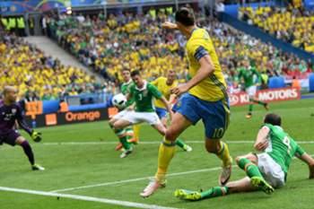 Ciaran Clark (C) of Ireland eyes the ball before scoring an own goal next to Zlatan Ibrahimovic (2nd R) of Sweden during the UEFA EURO 2016 group E preliminary round match between Ireland and Sweden at Stade de France in Saint-Denis, France, 13 June 2016. (RESTRICTIONS APPLY: For editorial news reporting purposes only. Not used for commercial or marketing purposes without prior written approval of UEFA. Images must appear as still images and must not emulate match action video footage. Photographs published in online publications (whether via the Internet or otherwise) shall have an interval of at least 20 seconds between the posting.