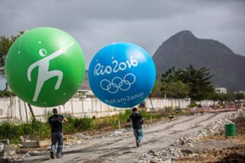 epa04341987 Workers carry huge balloons next to the Olympic Park in Barra two years prior to the Rio2016 Olympic Games, in Rio de Janeiro, Brazil, 05 August 2014. The balloons mark the locations in the City where the different stadiums will be built. EPA/MICHAEL KAPPELER