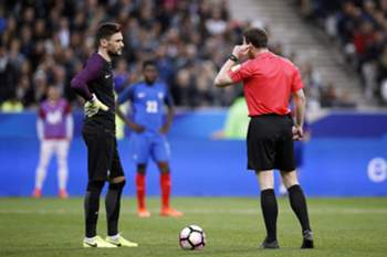 epa05876065 German referee Felix Zwayer (R) listens to his headset next to France's goalkeeper Hugo Lloris (L) during the international friendly soccer match between France and Spain at the Stade de France in Saint-Denis, near Paris, France, 28 March 2017.