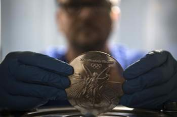 A worker holds a medal for the Rio Olympic Games at a coin factory in Rio de Janeiro, Brazil, on July 18, 2016. / AFP PHOTO /