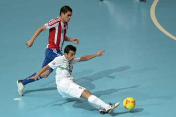 THAILAND, Bangkok : Portugal's paulinho (down) takes a shot next to Paraguay's Adolfo Salas (upper) during their play off for the quarter finals match during the FIFA Futsal World Cup 2012 at the Huamark Indoor Stadium in Bangkok on November 11, 2012. AFP PHOTO/ NICOLAS ASFOURI