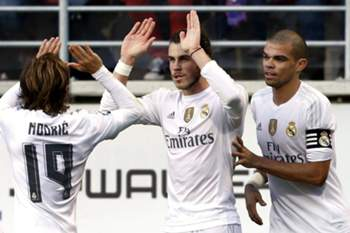 epa05047485 Real Madrid's Welsh midfielder Gareth Bale (C) celebrates with teammates, Croatian Luka Modric (L) and Portuguese Pepe, after scoring against Eibar during their Spanish Primera Division soccer match at Ipurua stadium in Eibar, Basque Country, northern Spain, 29 November 2015. EPA/Juan Herrero