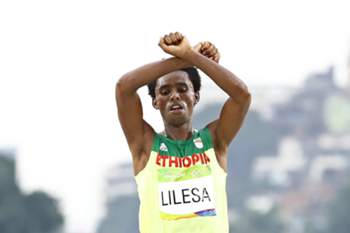 epa05505171 Feyisa Lilesa of Ethiopia celebrates while crossing the finish line to take the second place in the men's Marathon race of the Rio 2016 Olympic Games Athletics, Track and Field events at the Sambodromo in Rio de Janeiro, Brazil, 21 August 2016. EPA/DIEGO AZUBEL