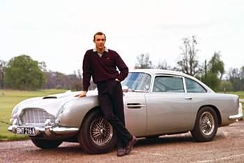 """É o carro mais mítico de James Bond, imortalizado no filme """"007 contra Goldfinger"""" em 1964. Tornou-se um emblema de sofisticação e sedimentou a introdução de «gadgets» como parte essencial da série."""
