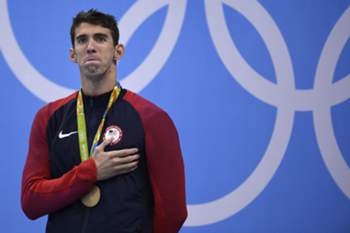 Gold medallist USA's Michael Phelps listens to his national anthem on the podium of the Men's 200m Individual Medley Final during the swimming event at the Rio 2016 Olympic Games at the Olympic Aquatics Stadium in Rio de Janeiro on August 11, 2016. / AFP PHOTO / Martin BUREAU
