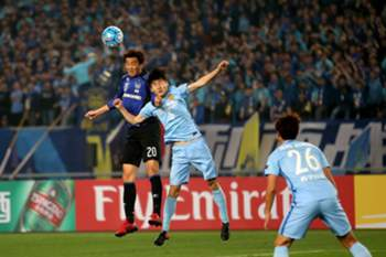 Zhou Yun (C) of Jiangsu FC fights for the ball with Shun Nagasawa (L) of Japan's Gamba Osaka during their AFC Champions League group stage football match in Nanjing, east China's Jiangsu province on April 11, 2017.