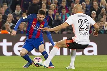 Lionel Messi tenta passar por Aymen Abdennour do Valência.