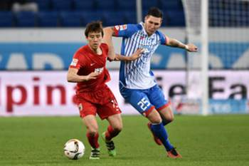 Niklas Süle (R) and FC Augsburg Ja-Cheol Koo fight for the ball during the German Bundesliga match between Hoffenheim and Augsburg in Hoffenheim, Germany 02 March 2016.