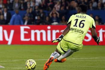 epa04764232 Edinson Cavani of Paris St Germain scores against goalkeeper Kossi Agassa of Reims during the French League 1 match at the Parc des Princes in Paris, France, 23 May 2015.