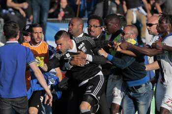 A security staff holds Lyon's goalkeeper Anthony Lopes (C) during scuffles at half-time between some of Lyon's players and Bastia supporters who invaded the pitch, during the French L1 football match Bastia (SCB) vs Lyon (OL) on April 16, 2017 in the Armand Cesari stadium in Bastia on the French Mediterranean island of Corsica. Before the match, dozens of Bastia fans invaded the pitch at their Armand Cesari stadium and attacked Lyon players as they warmed up for a French Ligue 1 game.