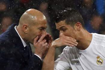 epa05256112 Real Madrid's Portuguese striker Cristiano Ronaldo (R) chats with his coach, French Zinedine Zidane (L) during the UEFA Champions League quarter final second leg match against Wolfsburg played at Santiago Bernabeu stadium in Madrid, Spain on 12 April 2016. EPA/KIKO HUESCA