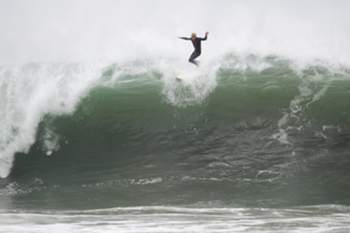 epa04732975 A surfboarder launches from a large wave while riding the huge surf in Newport Beach California, USA, 04 May 2015. The swell originated from a storm system off the New Zealand coast that brought nearly 20-foot waves to the area. EPA/EUGENE GARCIA