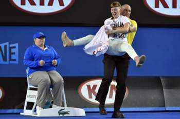 A protestor is carried away after activists interupt play and shout slogans demanding Australia opens for refugees during the men's finals match between Novak Djokovic of Serbia and Andy Murray of Britain at the Australian Open Grand Slam tennis tournament in Melbourne, Australia, 01 February 2015. 2015.