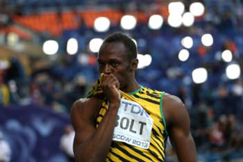 Jamaica's Usain Bolt kisses his shirt after winning the men's 200 metres final at the 2013 IAAF World Championships at the Luzhniki stadium in Moscow on August 17, 2013. AFP PHOTO / ADRIAN DENNIS