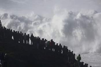 Bystanders watch giant waves at Nazare, Centre of Portugal, 11 December 2014. The next three days present weather conditions for the creation of giant waves in Nazare, where the American surfer Garrett McNamara won the record of having surfed the biggest wave in the world of 30 meters. MIGUEL A. LOPES/LUSA