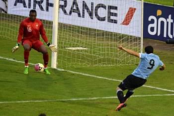 Uruguay's footballer Luis Suarez scores against France's goalkeeper Steve Mandanda during a friendly match at Centenario stadium in Montevideo on June 5, 2013. AFP PHOTO/Pablo PORCIUNCULA