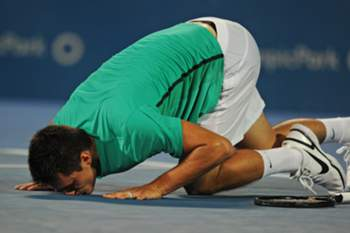 Bernard Tomic from Australia kisses the court after defeating Kevin Anderson of South Africa in the men's final at the Sydney International tennis tournament on January 12, 2013. IMAGE STRICTLY RESTRICTED TO EDITORIAL USE - STRICTLY NO COMMERCIAL USE AFP PHOTO / Greg WOOD