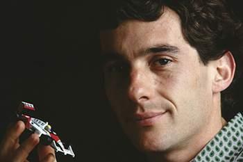 O piloto de F1 segura um modelo dum carro de corrida.