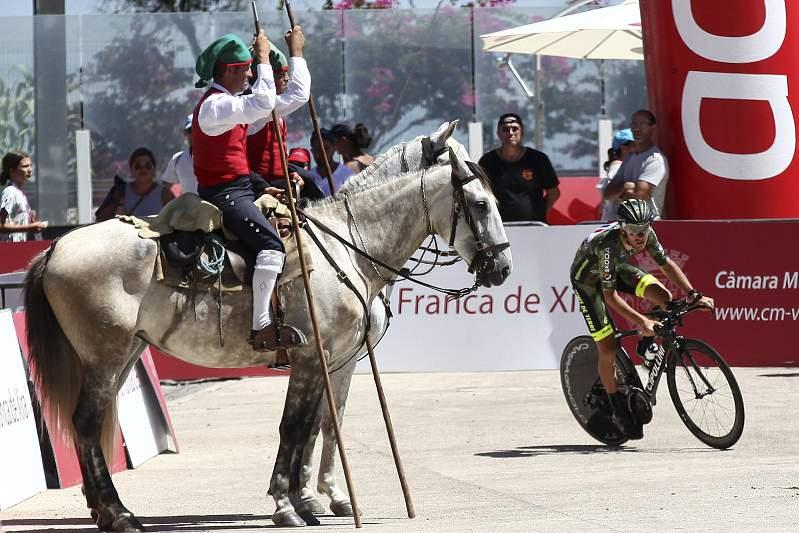 Um ciclista passa por dois campinos