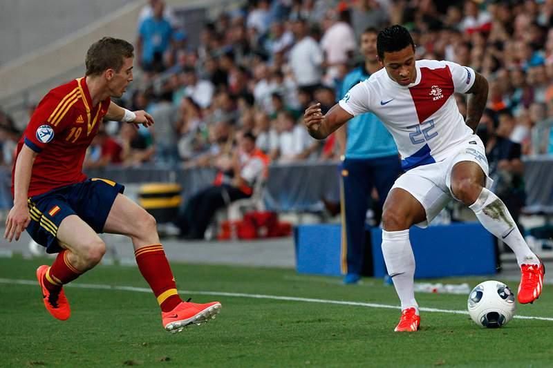Muniain de Espanha e Depay da Holanda disputam a bola.