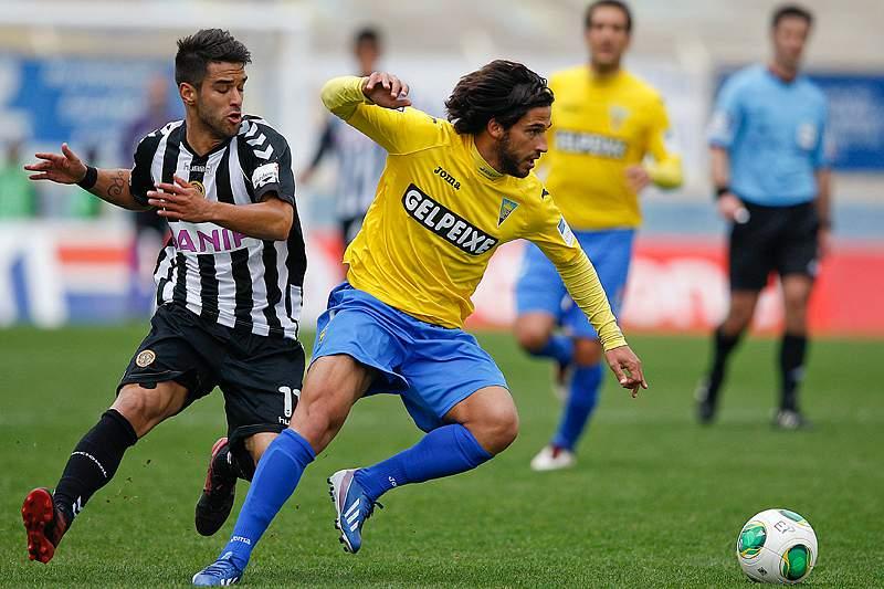 O jogador do Estoril, Tiago Gomes (D) disputa a bola com o jogador do Nacional, Candeias (E), durante o jogo da Primeira Liga de Futebol disputado no estádio António Coimbra da Mota, no Estoril, 07 de abril de 2013