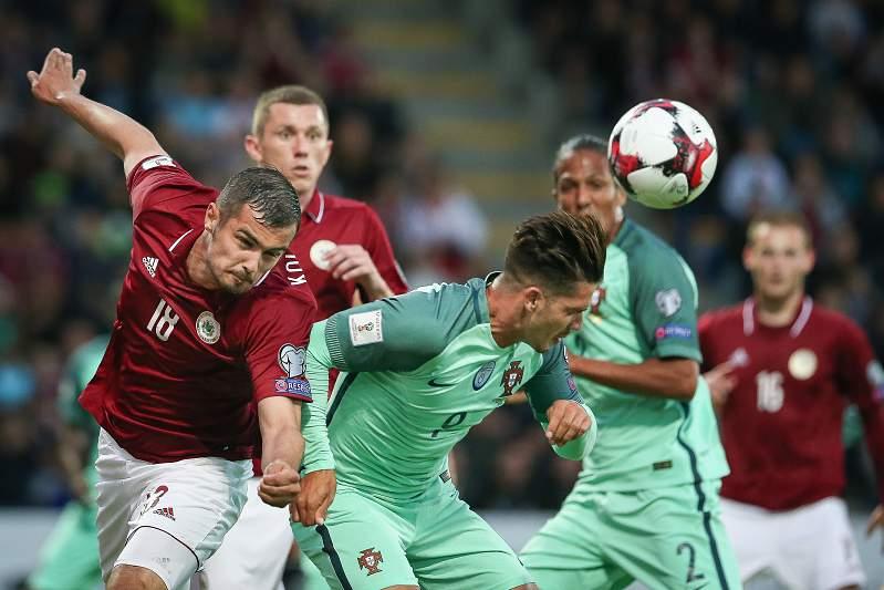 Kolesovs disputa uma bola com André Silva durante o jogo entre Letónia e Portugal