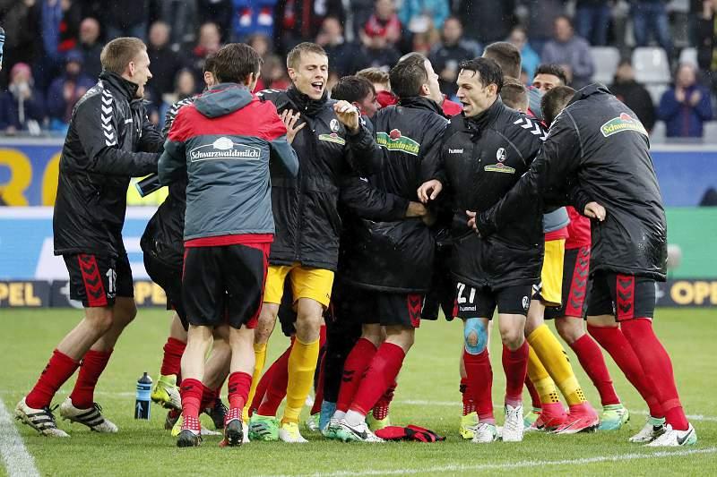 Jogadores do Friburgo celebram a vitória sobre o Schalke 04