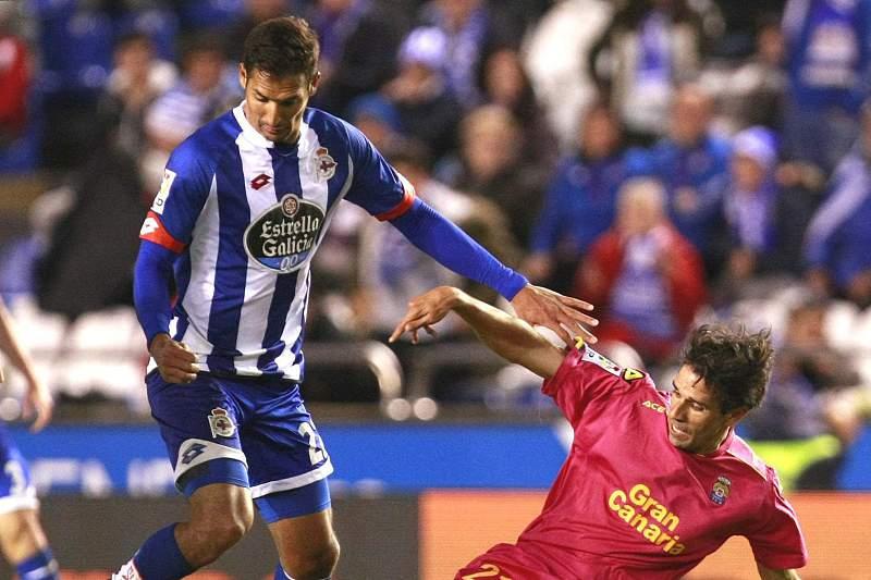 Celso Borges (E) disputa a bola com Juan Carlos Valeron
