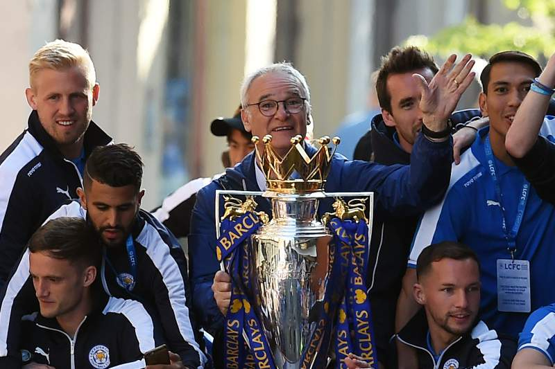 Leicester City's Italian manager Claudio Ranieri (C) holds the Premier league trophy as Leicester City's English striker Jamie Vardy raises his arms (R) to fans as the Leicester City team take part in an open-top bus parade through Leicester to celebrate winning the Premier League title on May 16, 2016. / AFP PHOTO / PAUL ELLIS