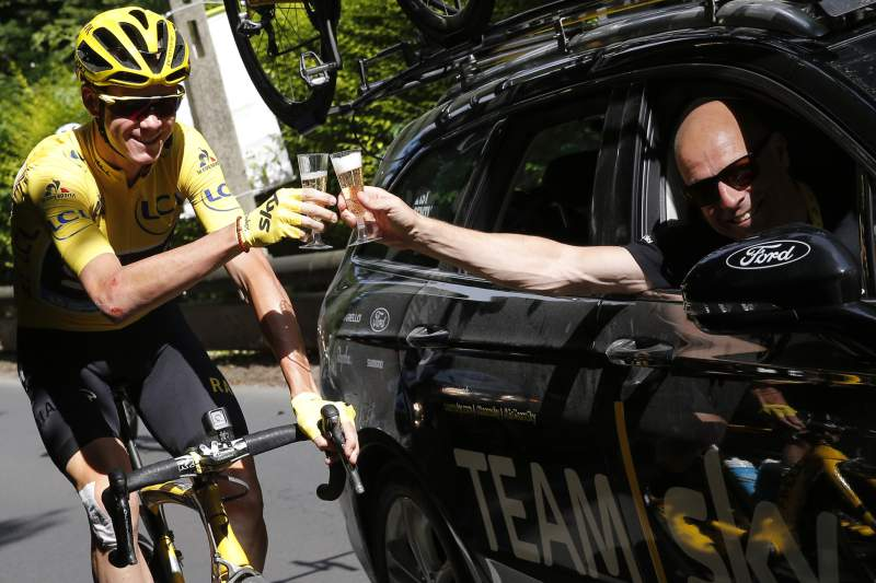 Great Britain's Christopher Froome (L), wearing the overall leader's yellow jersey, and Team Sky director Sir Dave Brailsford (R) drink a glass of champagne at the start of the 113 km twenty-first and last stage of the 103rd edition of the Tour de France cycling race on July 24, 2016 between Chantilly and Paris Champs-Elysees. / AFP PHOTO / Christophe Ena
