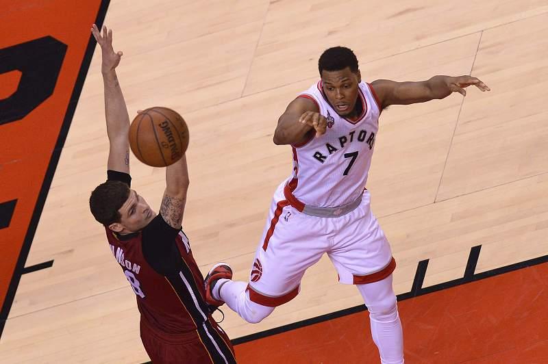 Kyle Lowry do Toronto Raptors passa por Tyler Johnson dos Miami Heat