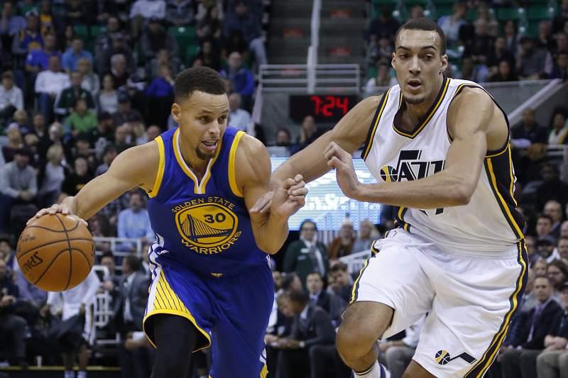 Stephen Curry passa por Rudy Gobert durante o jogo entre os Golden State Warriors e os Utah Jazz
