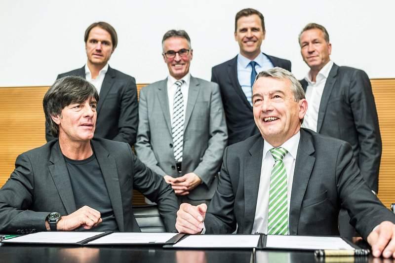 Joachim Loew com o presidente da Federação alemã Wolfgang Niersbach durante a cerimónia de renovação de contrato do selecionador alemão. Lá atrás estão Thomas Schneider, Helmut Sandrock, Oliver Bierhoff e Andreas Koepke.