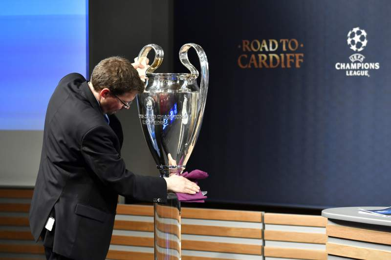 A man cleans the UEFA Champions League cup prior to the ceremony for the quarter-final draw of the quarter-final draw for the UEFA Champions League football tournament at the UEFA headquarters in Nyon on December 17, 2017. / AFP PHOTO / Fabrice COFFRINI