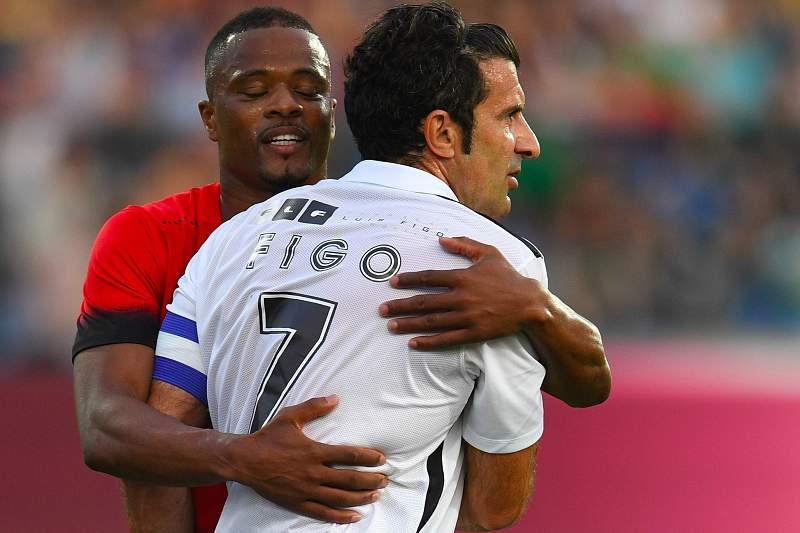 Patric Evra cumprimenta Luís Figo durante um jogo amigável