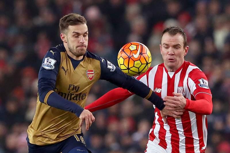 Aaron Ramsey disputa uma bola com Glenn Whelan durante um jogo entre Stoke City e Arsenal