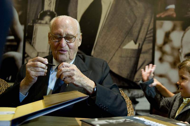 Former FIFA president Brazilian Joao Havelange stops autographing a book to talk with his great-grandson Roberto and great-grandaugther Julia (L) on February 24, 2011 during the launching of his biography in Rio de Janeiro, Brazil. Havelange was ahead of the FIFA during 24 years. AFP PHOTO/ANTONIO SCORZA