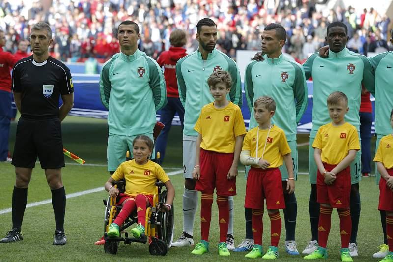 Cristiano Ronaldo entrou em campo acompanhado por uma criança em cadeira de rodas