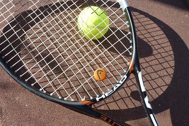 Veja uma raquete a bater numa bola de ténis em câmara lenta