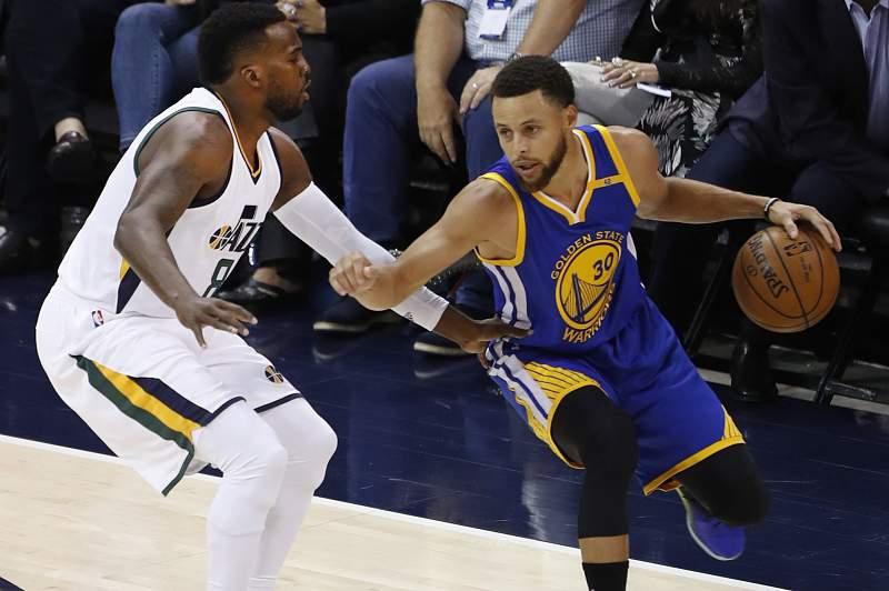 Golden State Warriors Stephen Curry (R) drives on Utah Jazz guard Shelvin Mack