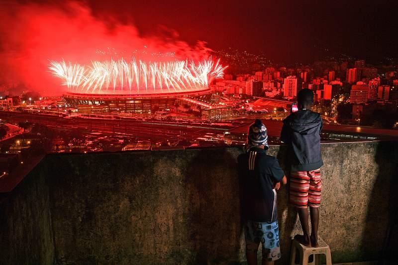 Crianças observam a festa de encerramento dos Jogos a partir de uma favela.