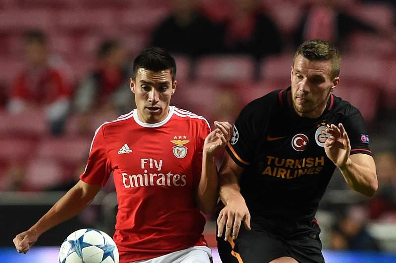 Gaitán disputa uma bola com Podolski no jogo entre Benfica e Galatasaray no Estádio da Luz