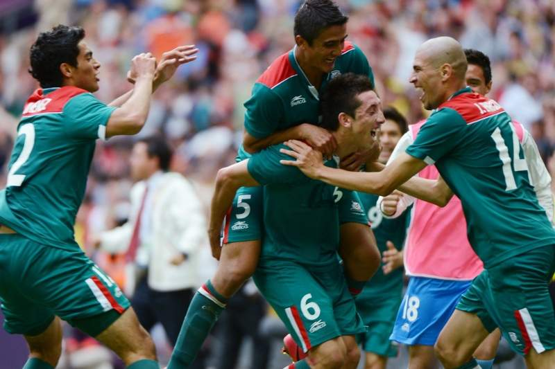 Mexico's midfielder Hector Herrera (6) celebrates with teammates after scoring a goal against Senegal during the Men's quarter final football match between Mexico and Senegal at Wembley Stadium in London, on August 4, 2012 during the London 2012 Olympic Games. AFP PHOTO / KHALED DESOUKI