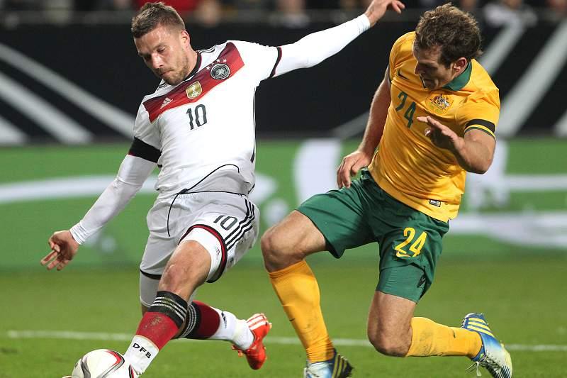 Lukas Podolski disputa a bola com Mark Bresciano